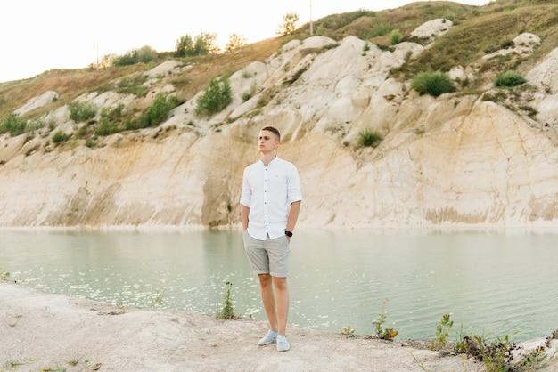 美しい若い男は日没時に青い湖と砂の近くで世界を旅します