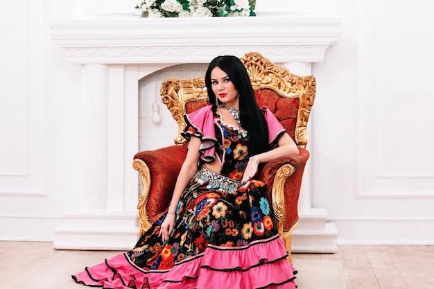Красивая молодая цыганка, сидящая в кресле