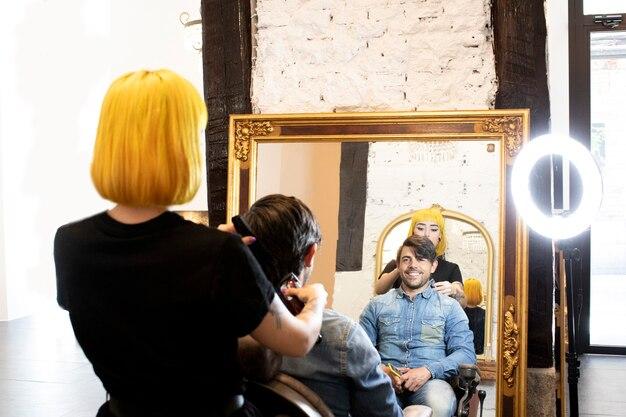 美しい若い美容師が美容院でハンサムな男に髪を切る