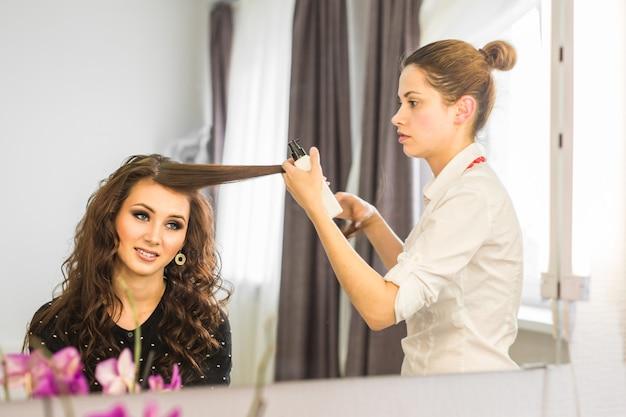 미용실에서 여성 고객에게 새로운 머리를 주는 아름다운 젊은 미용사.