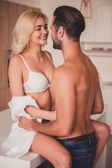 Beautiful young half-naked couple is looking at each other.