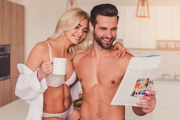 Beautiful young half-naked couple is reading a magazine.