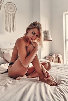 Красивая молодая полуобнаженная женщина в сексуальных кружевных черных трусиках позирует на кровати в спальне.