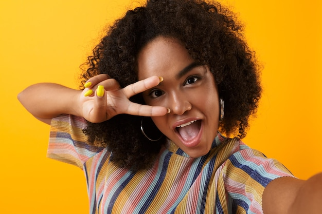 Beautiful young happy african cute girl posing isolated over yellow space take a selfie with peace gesture.