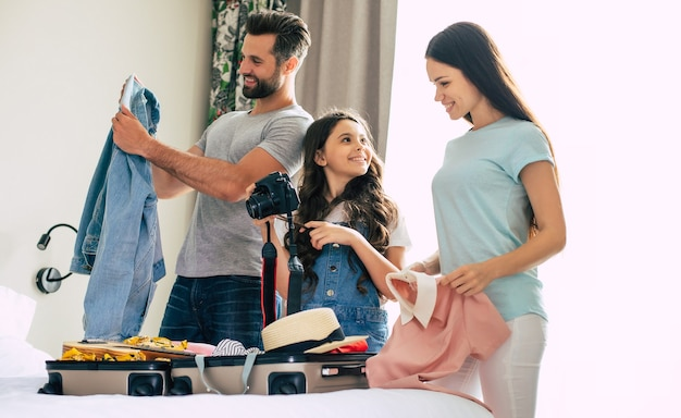 Красивая молодая счастливая и взволнованная семья в роскошном гостиничном номере во время распаковки