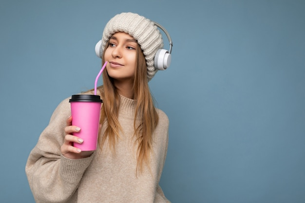 Beautiful young happy blonde woman wearing knitted hat beige sweater and white