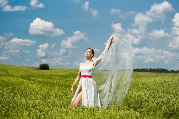緑のフィールドに美しい若い幸せな花嫁