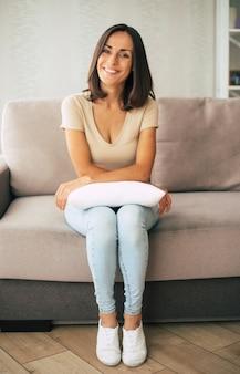 美しい若い幸せなブルネットの女性は、自宅のソファでリラックスして夢を見ています