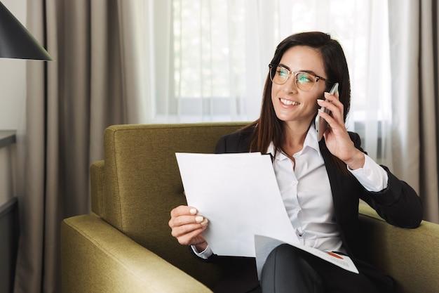 フォーマルな服を着て自宅で携帯電話で話している美しい若い幸せなビジネスウーマンは、ドキュメントを使用して作業します。