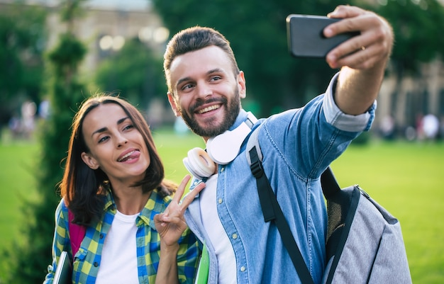 Beautiful young happy couple in casual clothes with backpacks are making selfie photo on smartphone