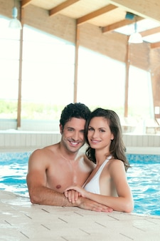 Beautiful young happy couple enjoy a pool at spa centre