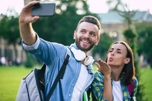 배낭 캐주얼 옷에서 아름 다운 젊은 행복 한 커플 스마트 폰에서 셀카 사진을 만들고 있습니다