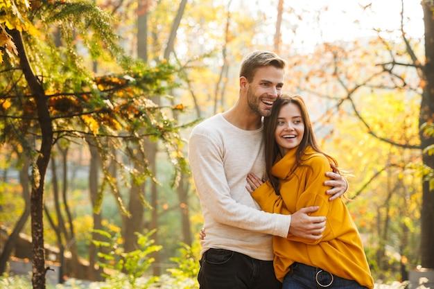 秋の公園で時間を過ごしながら抱きしめる愛の美しい若い幸せなカップル