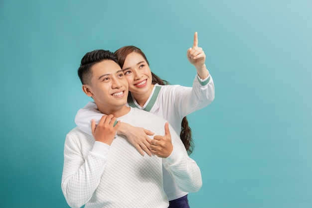 Beautiful young happy couple love smiling embracing point finger