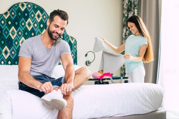 Beautiful young happy couple in a luxury hotel room in good mood are unpacking stuff
