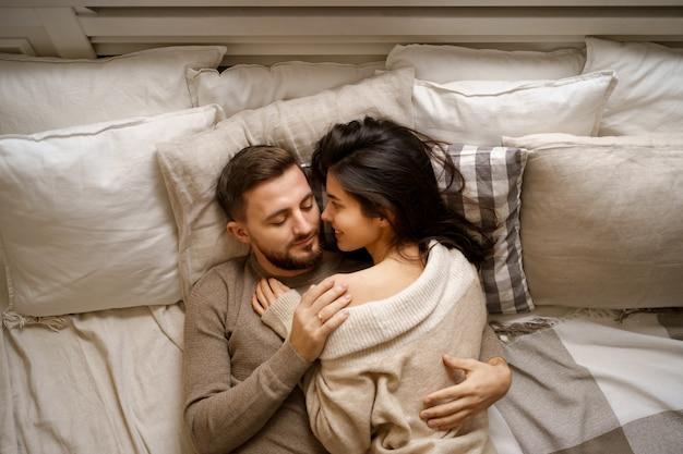 Bella giovane coppia felice rilassante a letto e sorridente, abbracciando