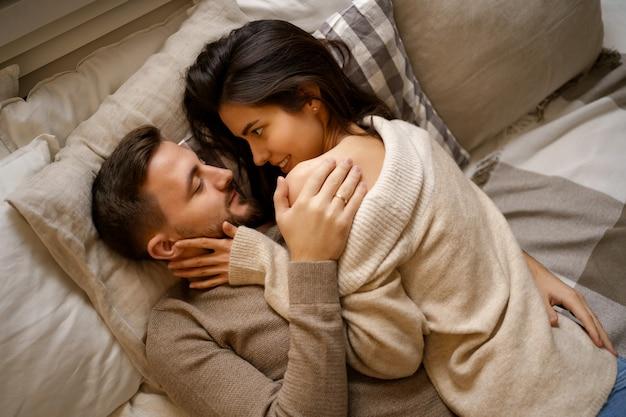 Красивая молодая счастливая пара расслабляется в постели и улыбается, обнимая