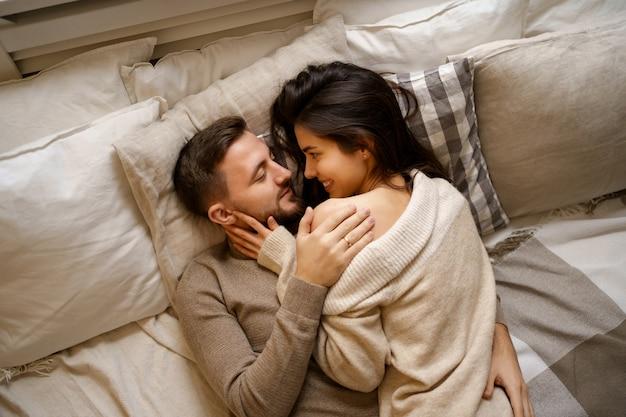 ベッドでリラックスし、笑顔で抱きしめて美しい若い幸せなカップル