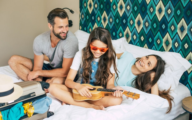 Beautiful young happy and excited family in a luxury hotel room while unpacking