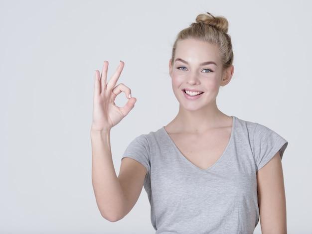 Красивая молодая счастливая взволнованная женщина показывает хорошо знаком на белом фоне