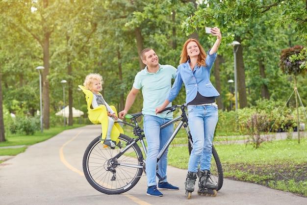 田舎でサイクリングやローラーブレードを楽しんでいる美しい若い幸せな家族。