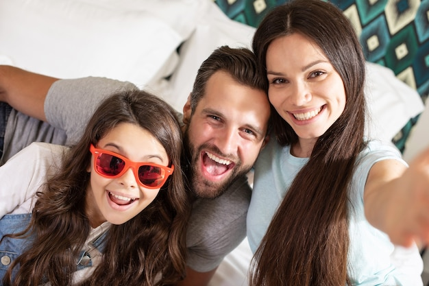 Beautiful young happy family making selfie photo in the bedroom and having fun together