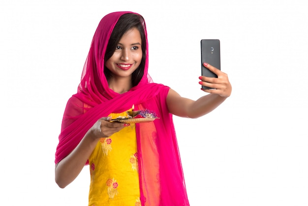 Beautiful young happy girl taking selfie with pooja thali using a mobile phone or smartphone