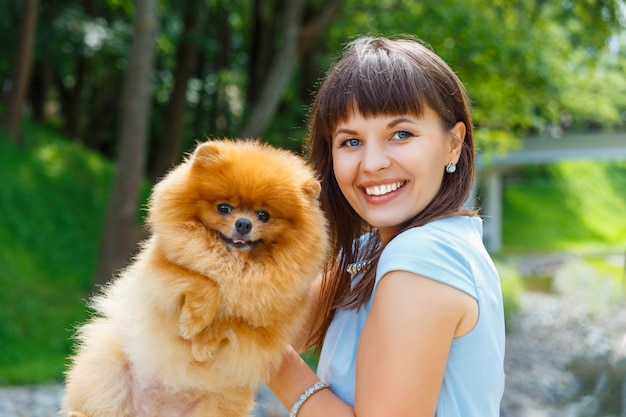 Beautiful young happy girl with spitz