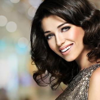 Bella giovane donna che ride felice con i capelli ricci marroni. modello di moda grazioso con trucco degli occhi scuri