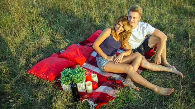화창한 여름날에 격자 무늬에 누워 피크닉을 즐기고 쉬고 있는 아름다운 젊은 행복한 부부. 카메라를 보고 웃 고입니다.