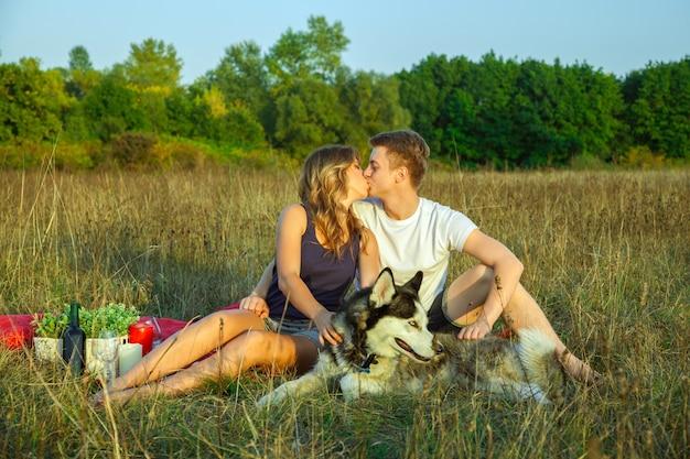 晴れた夏の日に野原で犬と一緒に格子縞の上に横たわってピクニックを楽しんで休んでいる美しい若い幸せな愛情のあるカップル。キスして楽しんでください。