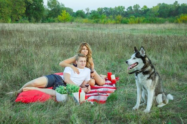 Красивая молодая счастливая любящая пара на пикнике, лежа на пледе с их собакой в поле в солнечный летний день, наслаждаясь, держа и пивая вино и отдыхая. смотрит на свою собаку и улыбается.