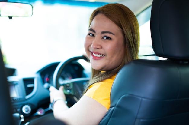 Красивая молодая счастливая улыбающаяся азиатская женщина за рулем своего нового автомобиля