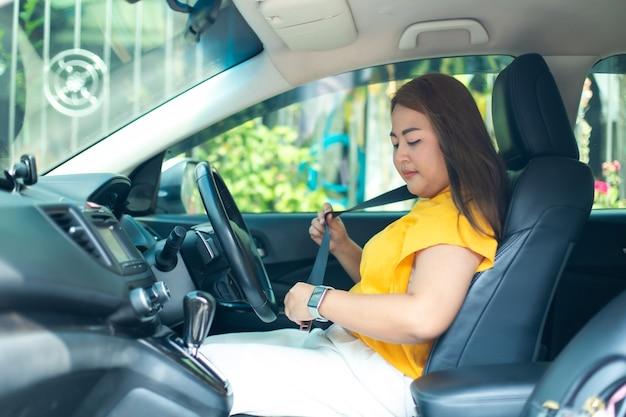 彼女の新しい車を運転する美しい若い幸せな笑顔のアジアの女性