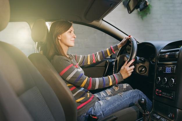 Una bella giovane donna europea dai capelli castani sorridente felice con una pelle sana e pulita vestita con una maglietta a righe si siede nella sua auto con interni neri. concetto di viaggio e di guida.