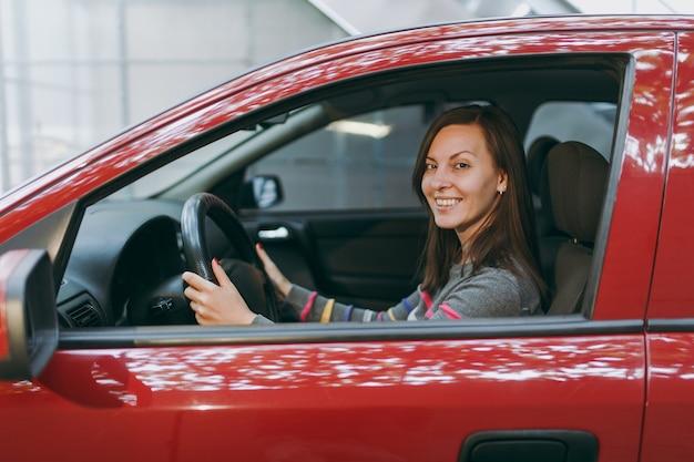 Una bella giovane donna europea dai capelli castani sorridente felice con una pelle sana e pulita vestita con una maglietta a righe si siede nella sua auto rossa con interni neri. concetto di viaggio e di guida.