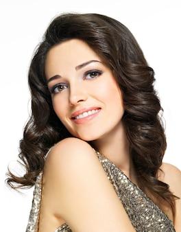 スタジオでポーズ茶色の巻き毛を持つ美しい若い幸せな笑顔の女性