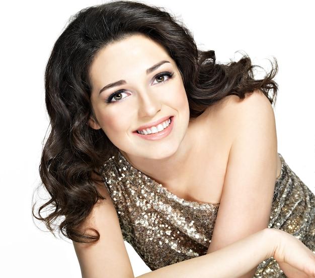 Bella giovane donna sorridente felice con la posa castana dei capelli ricci