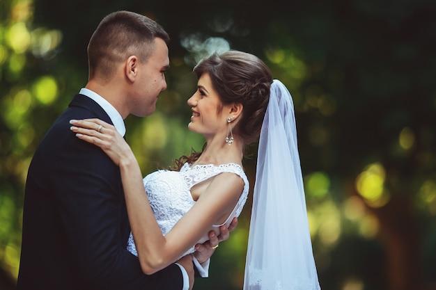 公園、屋外、緑の背景の美しい若い幸せな結婚式のカップル。新しい家族。