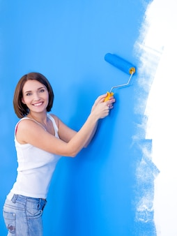 Beautiful young happy woman brushing the wall