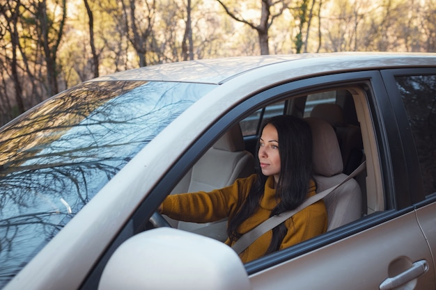 A beautiful young happy woman driving her car in the woods. the idea and concept of travel and discovery, fall getaway