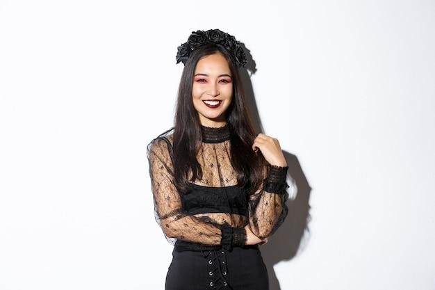 Bella giovane donna felice che gode della festa di halloween, sorridendo e guardando allegra mentre indossa il suo costume da strega malvagia per dolcetto o scherzetto, in piedi su sfondo bianco.