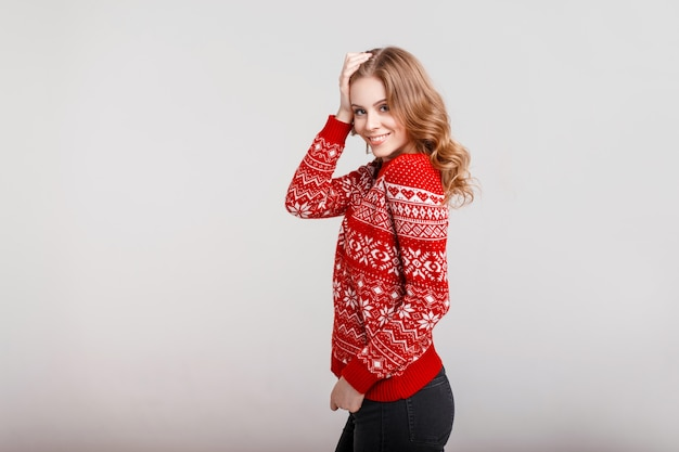 Beautiful young happy woman in a fashion vintage red sweater on a gray background in the studio