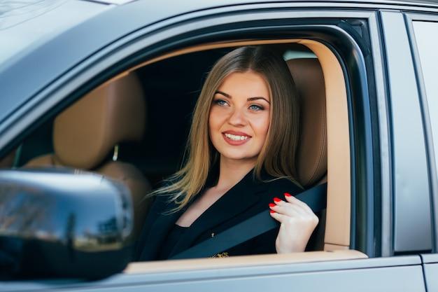 美しい若い幸せな女性が車のシートベルトを締める
