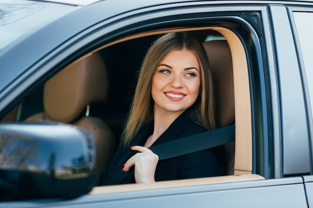 Bella giovane donna felice allaccia una cintura di sicurezza in macchina