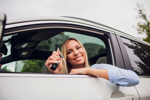キー-屋外で新しい車の中で美しい若い幸せな女