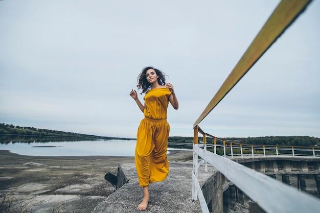 Красивая молодая счастливая женщина идет по перилам конструкции в ярком платье