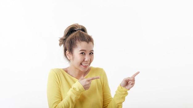 横を指している美しい若い幸せな女性