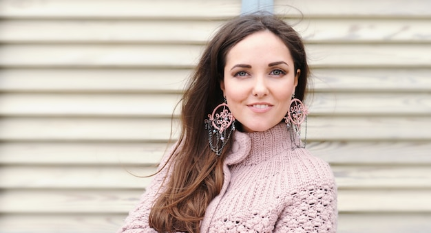 Beautiful young happy woman portrait, cute gentle sweater and handmade boho style earrings
