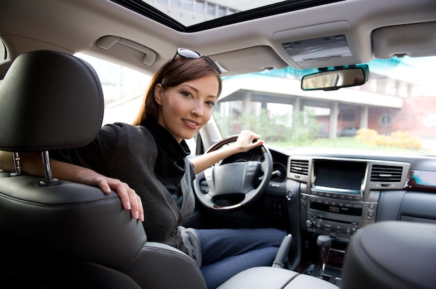 新しい車の中でポーズをとって美しい若い幸せな女性
